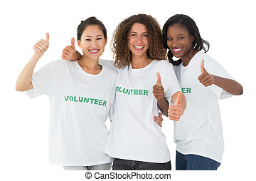 Happy team of volunteers giving thumbs up at camera