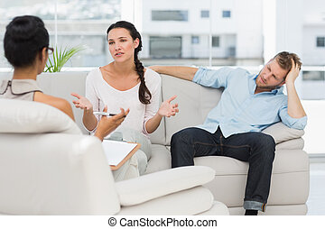 Angry couple sitting on couch talking to therapist in...