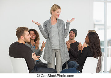 Rehab group applauding happy woman standing up at therapy...