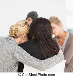 Women hugging in rehab group at therapy session