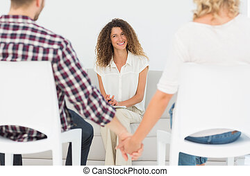Happy therapist smiling at reconciled couple holding hands...