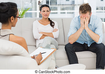 Unhappy couple sitting on sofa at therapy session in...