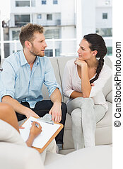 Unhappy couple talking at therapy session in therapists...