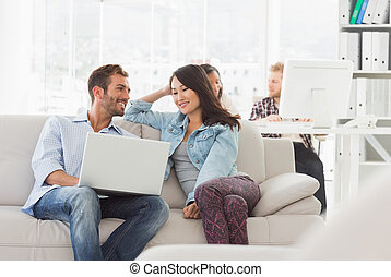 Smiling designers working together on laptop on the couch in...