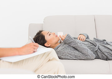 Therapist taking notes on her crying patient on the couch