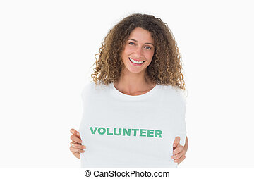 Smiling volunteer showing her tshirt to camera on white...