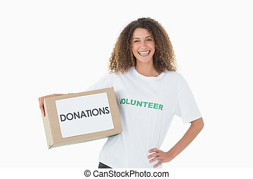 Smiling volunteer holding a box of donations with hand on...
