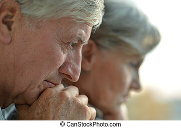Close-up portrait of a sad elder couple on white background
