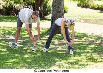 Fit couple exercising in park - Full length of fit couple...
