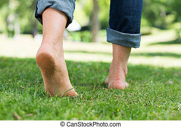 Woman walking on grass - Low section of woman walking on...