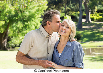 Man kissing woman in park