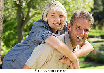 Man giving woman a piggyback ride - Portrait of happy man...