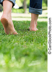 Woman walking on grassy land - Low section of woman walking...