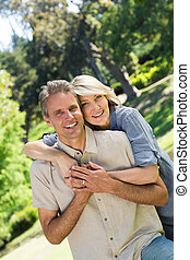 Couple with arm around in park - Portrait of happy couple...