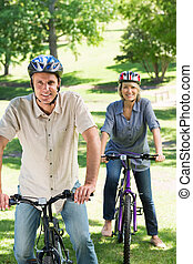 Couple riding cycles in park - Portrait of happy couple...