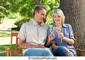 Couple toasting wine glasses in park - Loving couple...