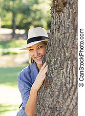 Smiling woman hiding behind tree trunk - Portrait of smiling...