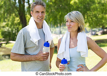 Fit couple in the park - Fit couple with towels and water...