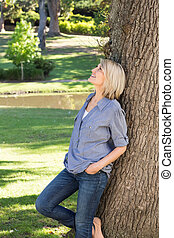 Thoughtful woman in park - Thoughtful woman leaning on tree...