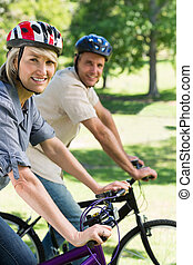 Couple riding bicycles in a park - Portrait of beautiful...