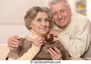 Cute old couple drinking tea at home