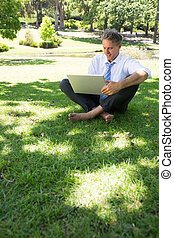 Businessman using laptop outdoors - Full length of...