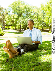 Businessman surfing on laptop - Mature businessman using...