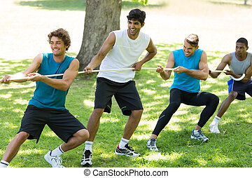 Male friends playing tug of war - Smiling male friends...