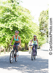 Sporty women riding bicycles