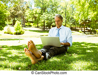Businessman using laptop while relaxing in park - Full...