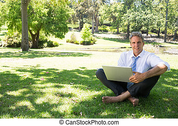 businessman with laptop sitting on - Full length portrait of...