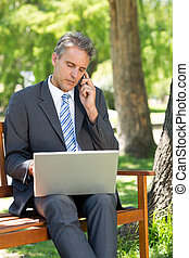 Businessman answering cellphone while using laptop - Mature...