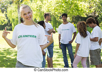 Beautiful volunteer pointing at tshirt - Beautiful female...