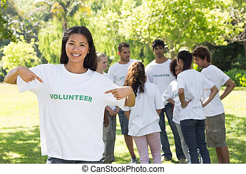 Beautiful volunteer pointing at tshirt - Portrait of...