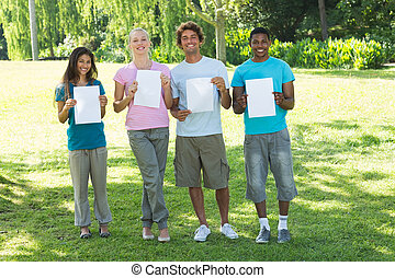 Friends holding blank papers on campus
