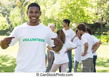 Volunteer pointing at tshirt in park - Happy male volunteer...