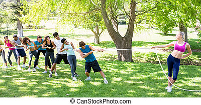 Woman playing tug of war with friends - Fit woman playing...