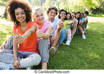 University students gesturing thumbs up - Portrait of...