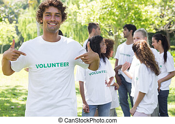Portrait of volunteer pointing at tshirt - Portrait of male...