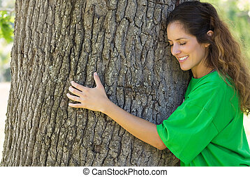 Environmentalist hugging tree trunk - Smiling female...
