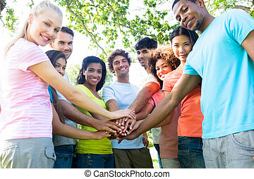 Multiethnic friends stacking hands - Group portrait of...