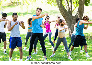 Friends exercising in park - Group of multiethnic friends...