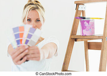 Woman holding blurred color swatches in new house - Portrait...