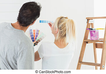 Rear view of a couple choosing color for painting a room...