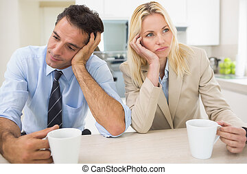 Well dressed thoughtful couple with coffee cups in kitchen -...
