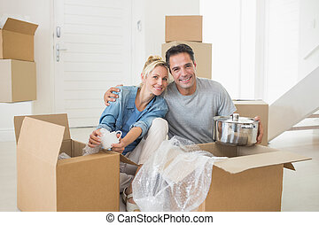 Smiling couple unpacking boxes in a new house - Portrait of...