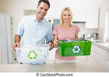 Smiling couple carrying recycling containers in kitchen -...