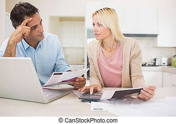 Worried couple with bills and laptop in kitchen - Worried...