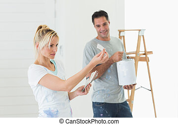 Couple with color swatches and ladder in a new house - Young...