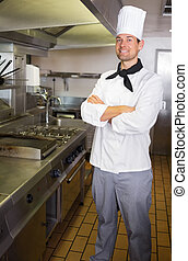 Smiling male cook with arms crossed in the kitchen -...